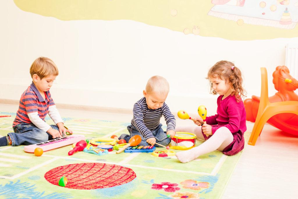 3 Kleinkinder spielen auf dem Boden mit Musikinstrumenten