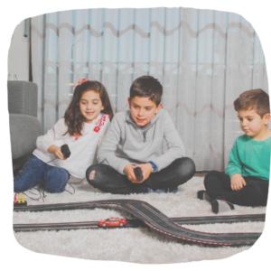 2 Jugs und 1 Mädchen spielen zusammen mit einer Autorennbahn