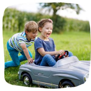Ein Junge scheibt ein Mädchen im Elekroauto für Kinder an