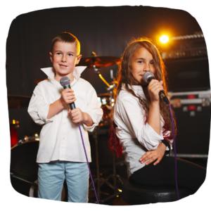 Junge und Mädchen singen mit richtigen Mirkofons im Tonstudio