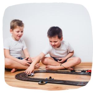 Zwei Jungs spielen mit einer Autorennbahn