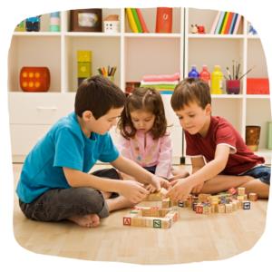 Drei Kinder spielen mit Bauklötzen