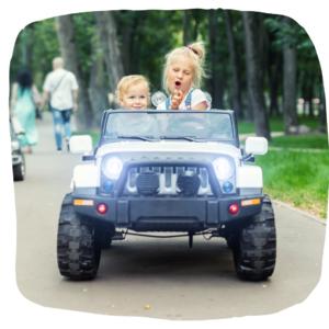 Zwei Mädchen sitzen in einem Spielzeugauto