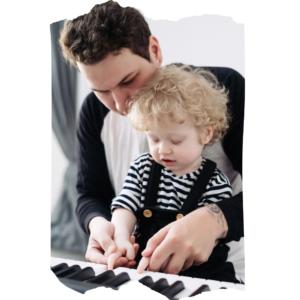 Junger Vater hat Kleinkind auf dem Schoß und spielt mit ihm Klavier