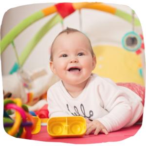 Baby liegt mit Spielzeug auf einer Decke und lacht
