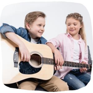 Junge und Mädchen sitzen auf dem Sofa mit einer Gitarre in der Hand