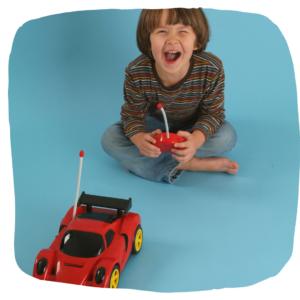Junge spielt mit ferngesteuerten Auto und lacht