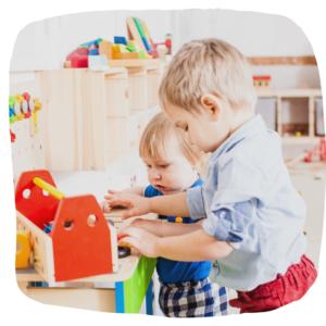 Zwei kleine Jungs spielen mit Holzspielzeug