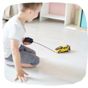 Kind spielt auf dem Boden mit ferngesteurtem auto