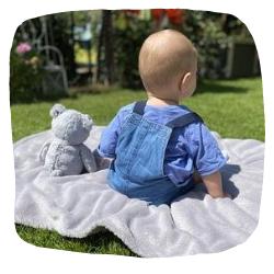 Kuscheltiere-für-babys-Junge-sitz-im-Gras-mit-Teddy