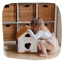 Ein Mädchen spielt mit einem Puppenhaus