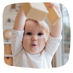 Ein Kleinkind hält einen Block in die Höhe