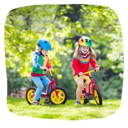 Ein Mädchen und ein Junge auf Laufrädern