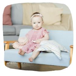 Baby sitzt auf einer kleinen Couch