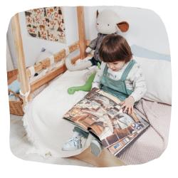 Ein kleiner Junge sitzt auf seinem Bett und schaut sich ein Buch an.