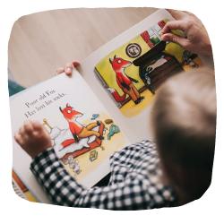 Ein Kind und ein Erwachsener lesen ein Buch.