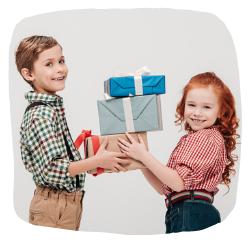 Ein Mädchen und ein Junge halten zusammen drei Geschenke in die Höhe.