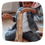 Ein Kind baut einen Jenga Turm.