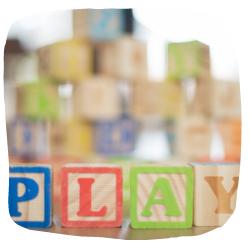Bauklötze, die das Wort Play buchstabieren.