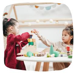 2 Mädchen sitzen am Tisch und spielen zusammen mit Klötzen.