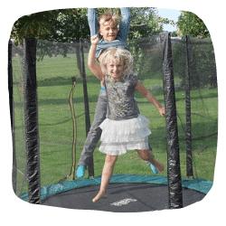 Zwei Kinder springen auf einem Trampolin im Garten
