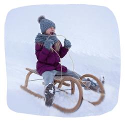 Ein Mädchen fährt auf einem Schlitten