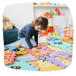 Ein Mädchen spielt mit einer Puzzlematte.