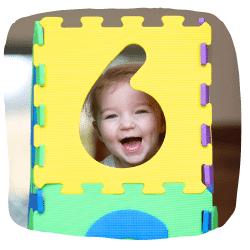 Ein Mädchen schaut durch eine aufgestellte Puzzlematte hindurch.