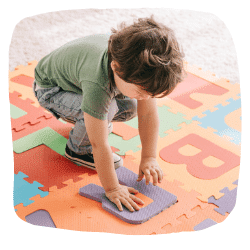 Ein Junge spielt mit einem Puzzleteppich.