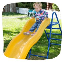 Ein Mädchen rutscht auf einer gelben Rutsche