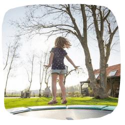 Ein Kind springt im Garten auf dem Trampolin