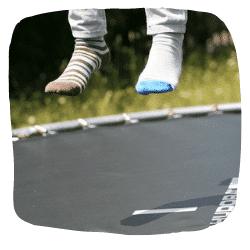Ein Trampolin auf dem zwei Füße in der Luft zu sehen sind.