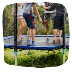 Vier Kinder springen auf einem Trampolin im Garten.