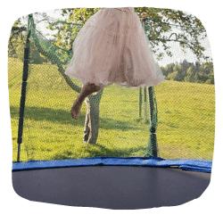 Ein Mädchen springt im Garten auf dem Trampolin.