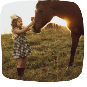 Mädchen streichelt ein Pferd