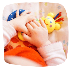 Ein Baby spielt auf einer Decke mit Spielzeug