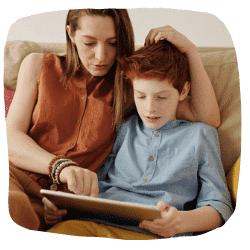 Eine Frau sitzt mit ihrem Sohn auf dem Sofa und schaut in das Tablet.