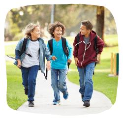 3 Jungs rennen auf einem Gehweg