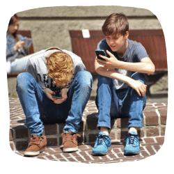 2 Jungs sitzen auf einem Bordstein und spielen mit dem Handy