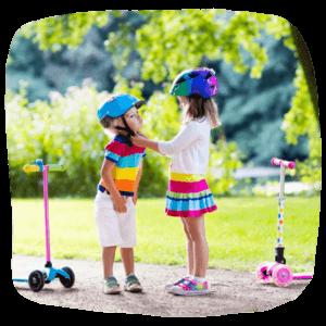 Kinder mit Rollern im Park