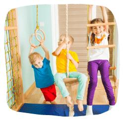 Drei Kinder turnen an einer Turnwand.