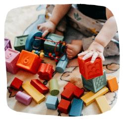 Ein Kind sitzt auf einer Decke und spielt mit Bauklötzen