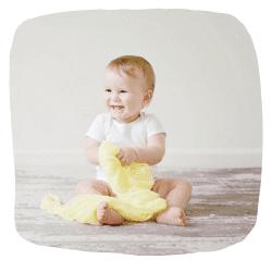 Ein Baby sitzt lachend auf dem Boden.