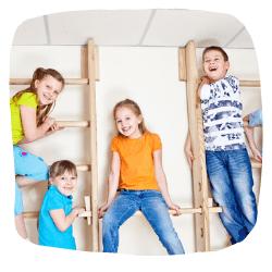 Vier Kinder sind auf einer Turnwand und schauen in die Kamera.