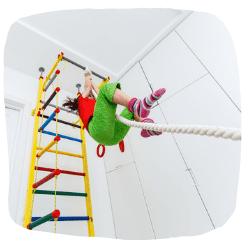 Ein Kind turnt auf einer Turnwand an einem Seil.
