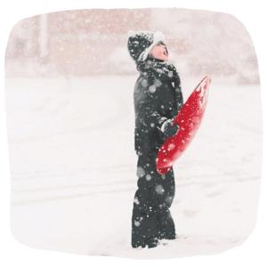 Ein Junge steht im Schneegestöber und hält ein Schlitten