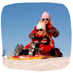 Zwei Mädchen fahren mit einem Schlitten