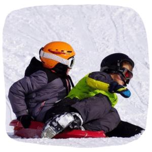 Zwei Kinder fahren mit einem Schlitten