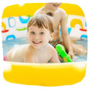 Zwei Kinder spielen in einem Planschbecken