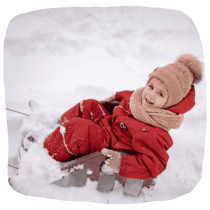 Ein Kind sitzt auf einem Schlitten
